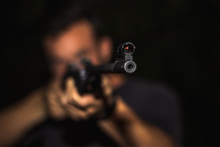 close up view of a man holding a rifle