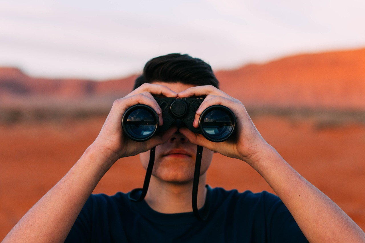 man holding a binocular