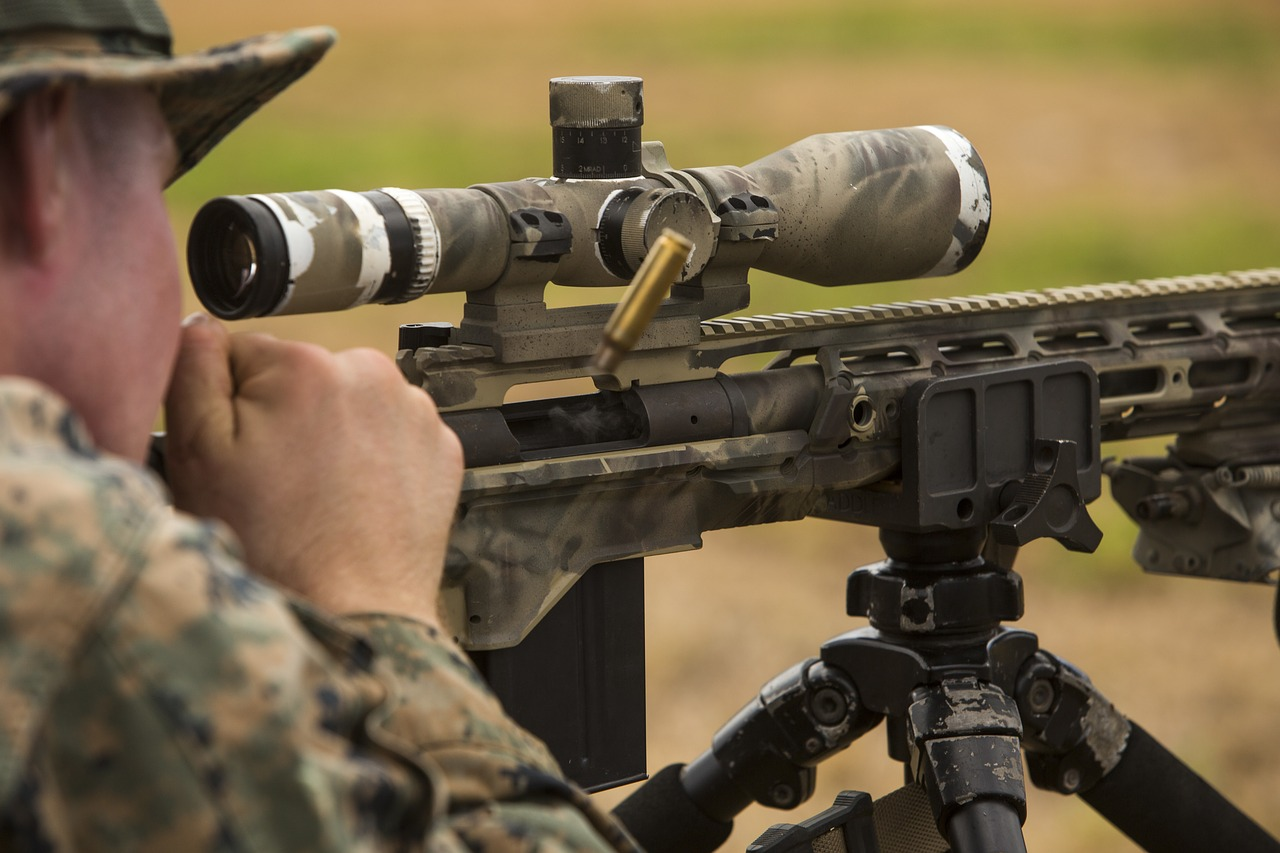 a marine looking through one of the first focal plane scopes while shooting the gun