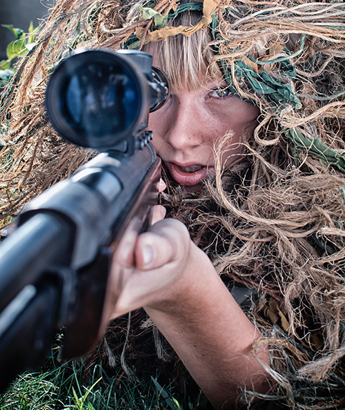 Woman aiming a gun using a prism scope