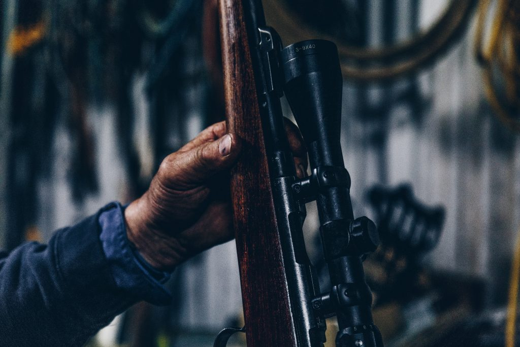 a person holding a rifle with scope