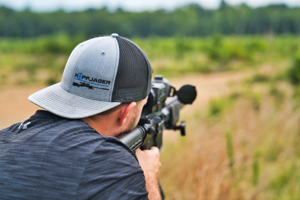 a man wearing a cap looking through the scope attached to the rifle