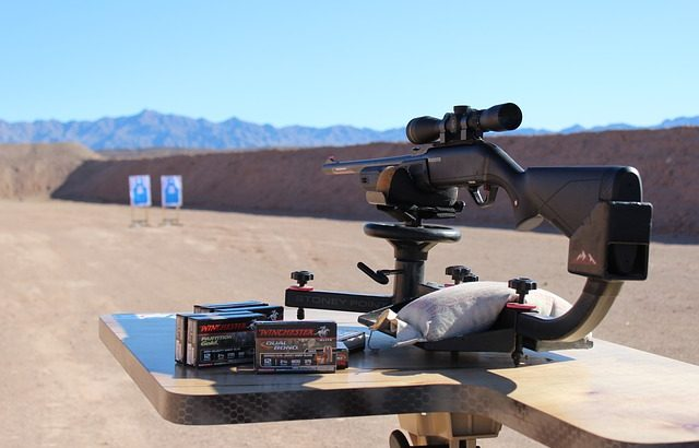 a gun with scope set up on long range target shooting area