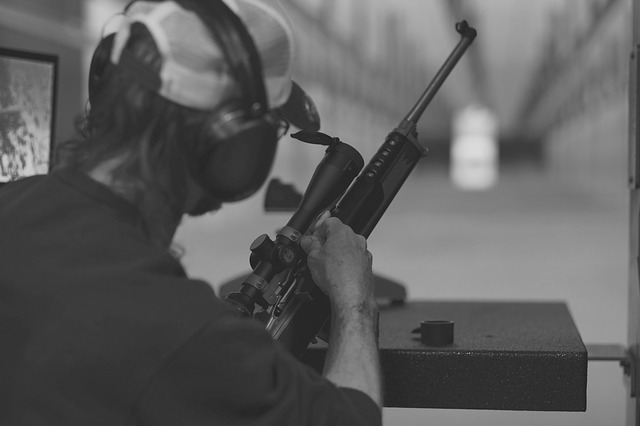 a man using a rifle with scope during target shooting practice
