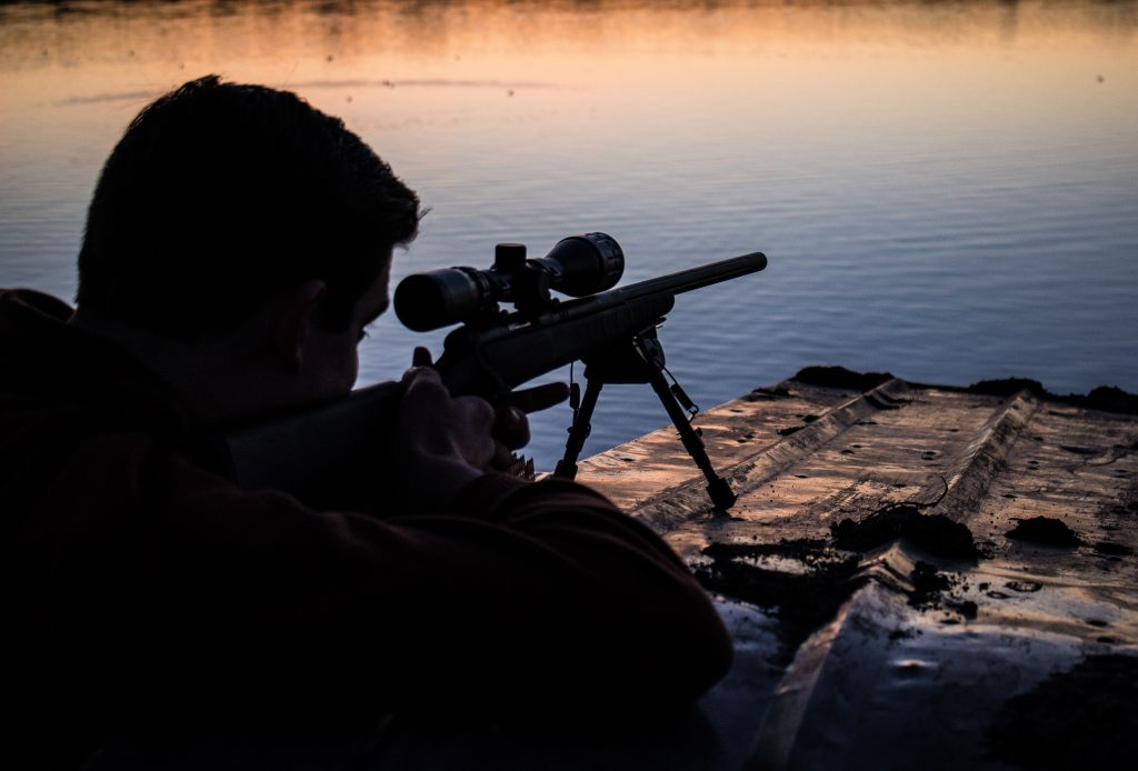 a man looking through the sniper scope